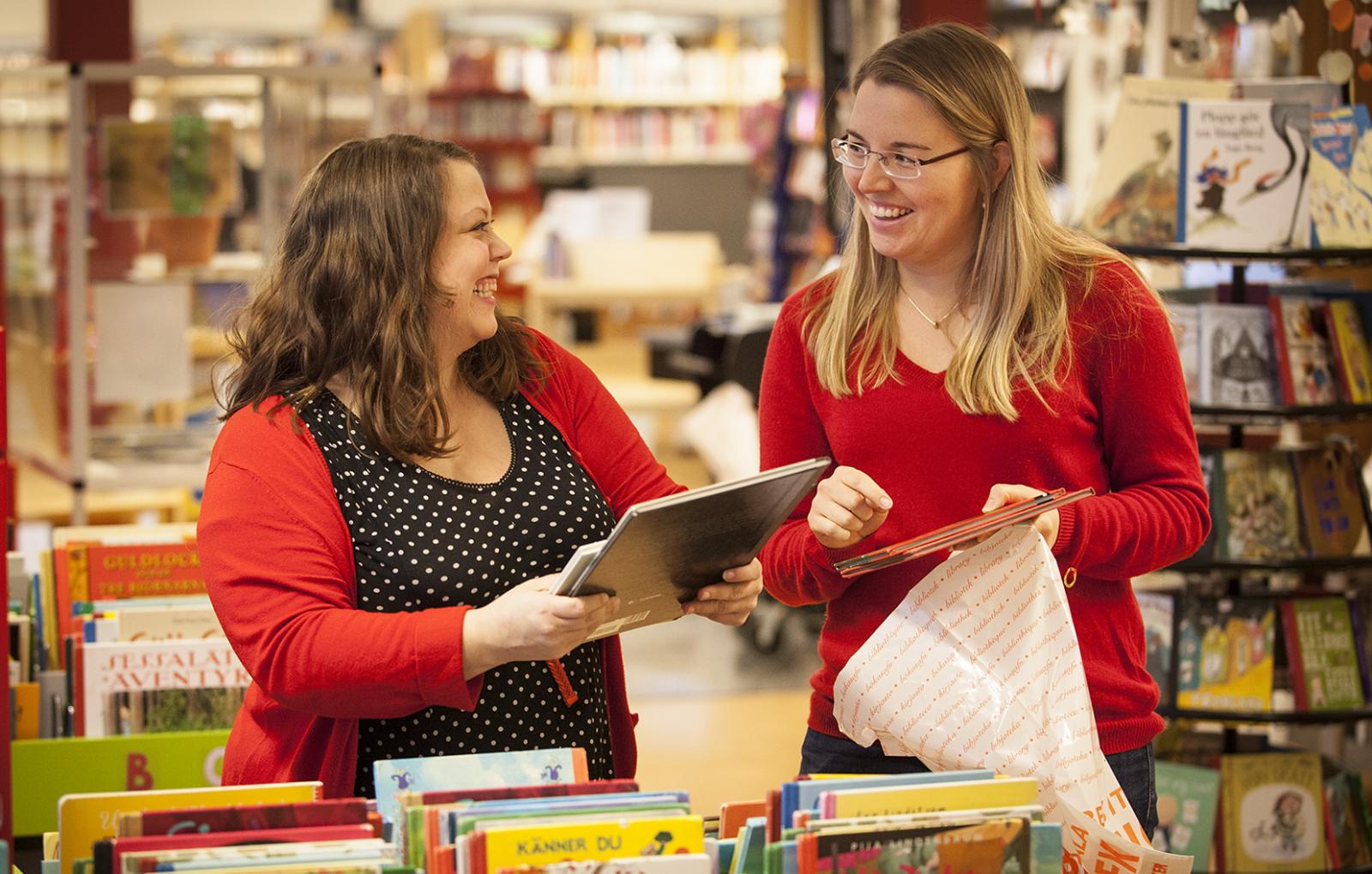 Två leende kvinnor, båda i röda tröjor, står i ett bibliotek och lägger böcker i en kasse.