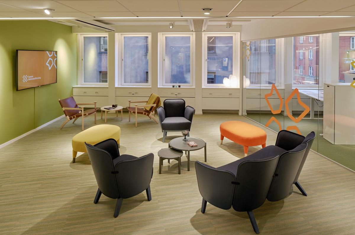 Kontorsmiljö möblerad med färgglad sittgrupp.