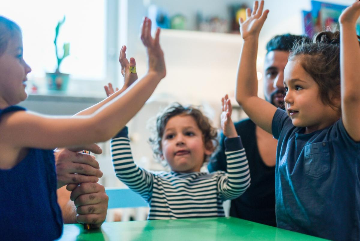 Flera stycken barn står runt ett bord och sträcker upp händerna i luften.