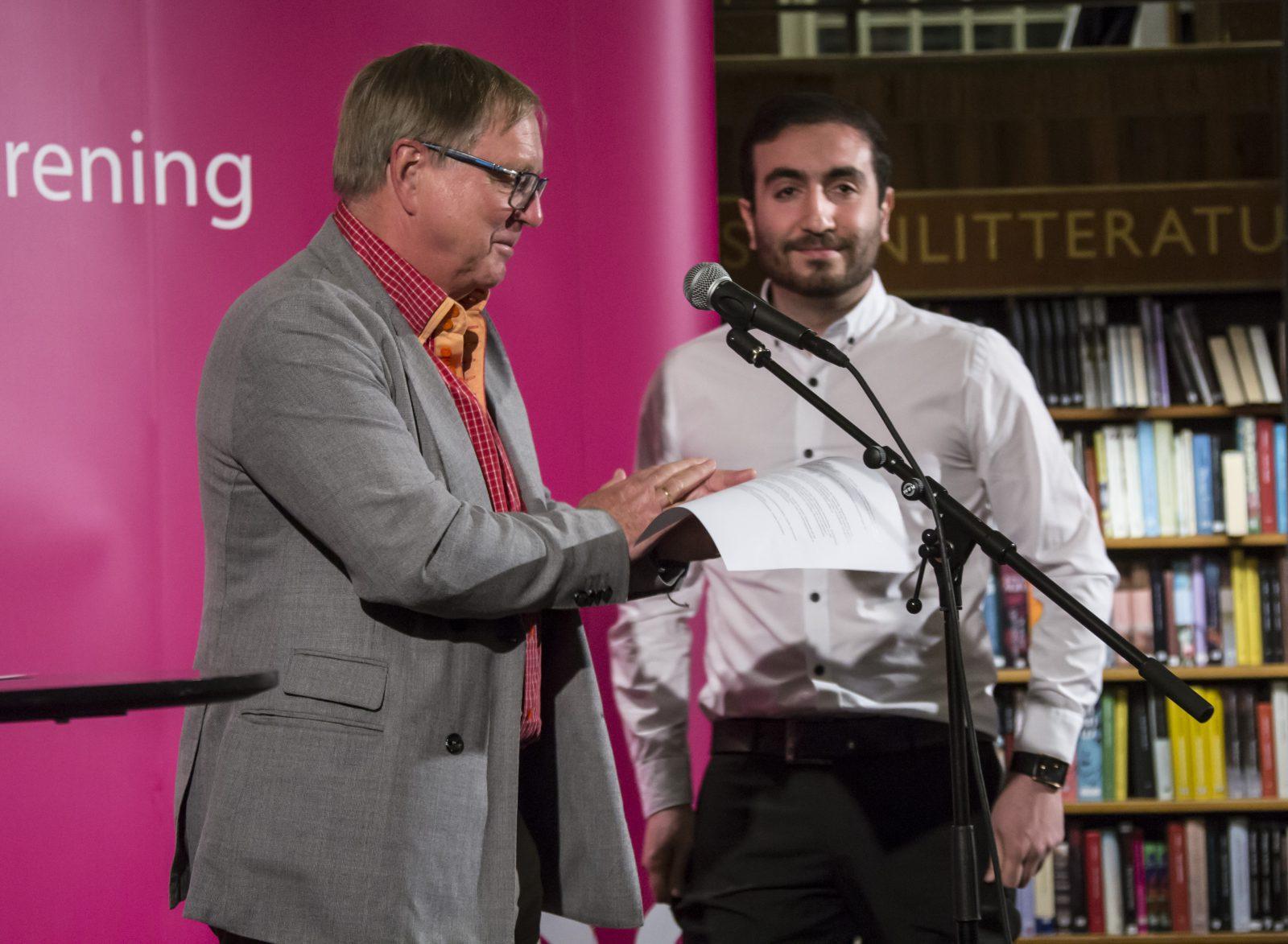 Två män på en scen, den ena läser något för den andra från ett papper.