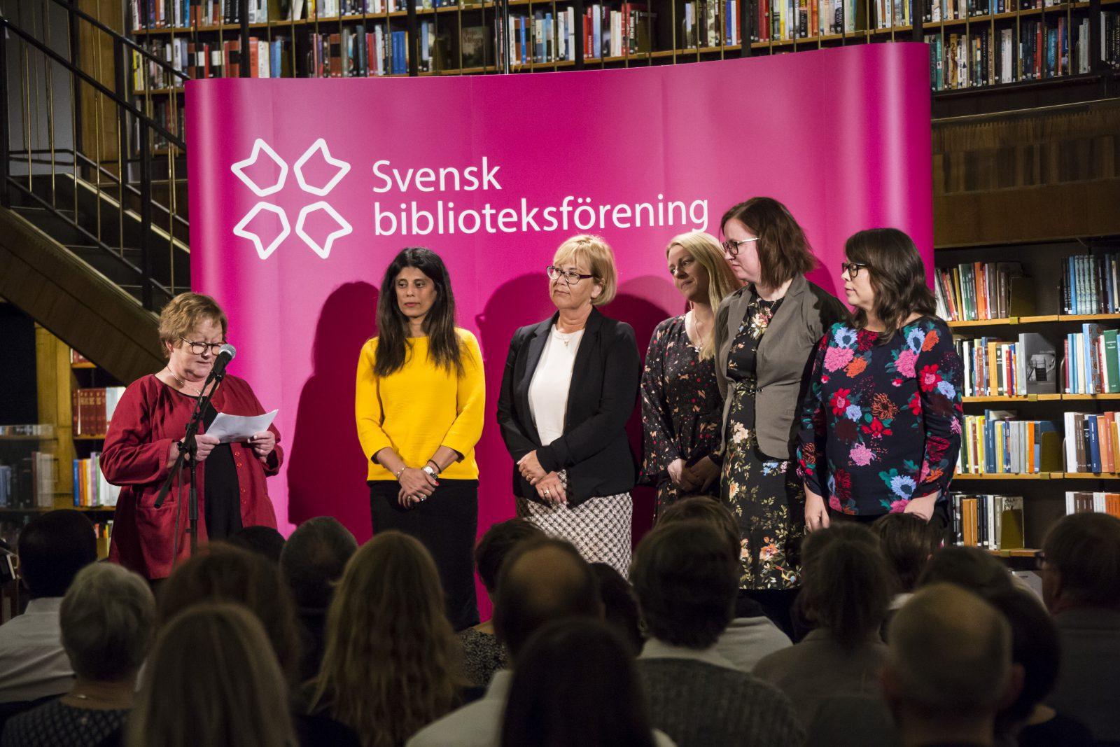 Sex personer står på en scen, en läser från ett papper medan de andra lyssnar.