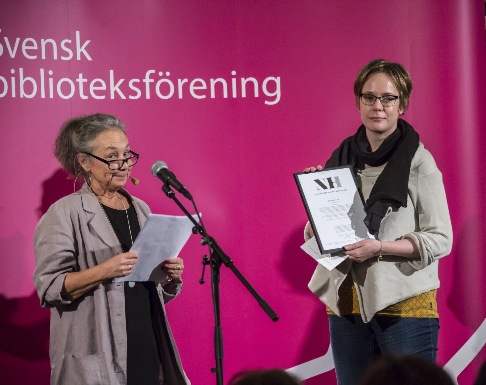 Två kvinnor på scen, en läser från ett papper och den andra håller ett diplom.